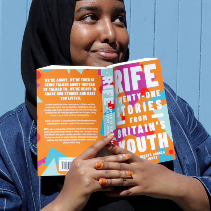 Asmaa Jama holding a copy of the Rife: Twenty-One Stories from Britain's Youth book
